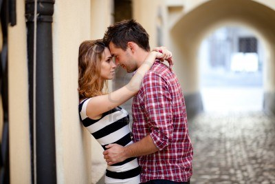 14351309-young-couple-in-love-hugging-in-the-old-part-of-town